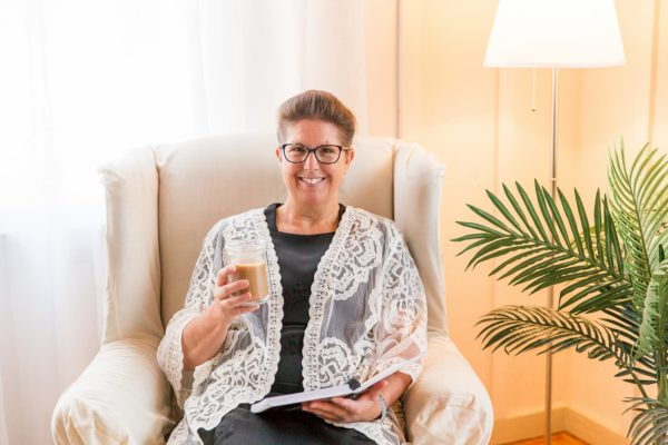 Smiling Woman with Open Planner and Coffee Sitting in Chair
